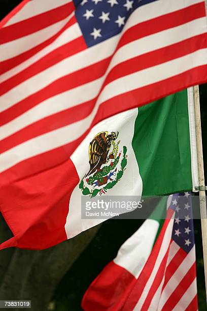Mexican and American flags fly near an auto dealership April 6 2007 in Los Angeles California As the demographics of large cities in the US continue...