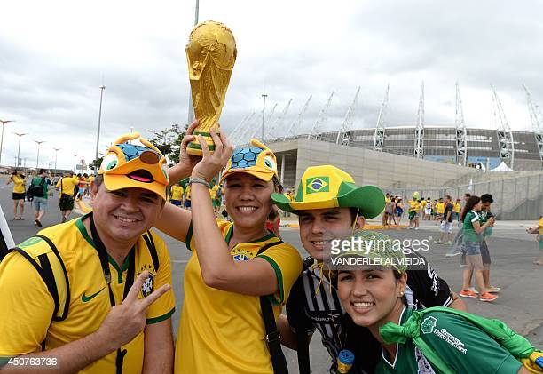 Mexican and Brazilian fans pose with a replica of the World Cup trophy on arrival for a Group A football match between Brazil and Mexico in the...