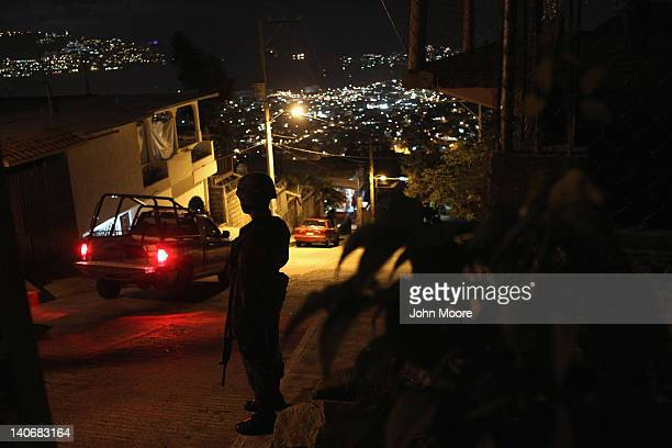 Mexican army soldier stands guard at a suspected drug-related murder site March 3, 2012 in Acapulco, Mexico. A forensics team excavated five corpses...