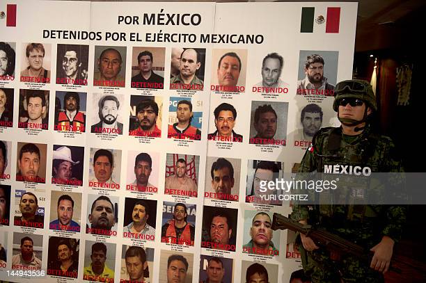 A Mexican army soldier stands guard beside a placard with pictures of alleged drug cartels members already arrested during the presentation to the...