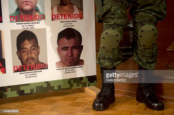 Mexican army soldier stands guard beside a placard with pictures of alleged drug cartels members already arrested during the presentation to the...