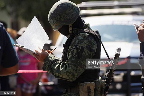 Mexican army soldier takes notes at the site of a suspected drug-related double execution on March 2, 2012 in Acapulco, Mexico. Drug violence has...