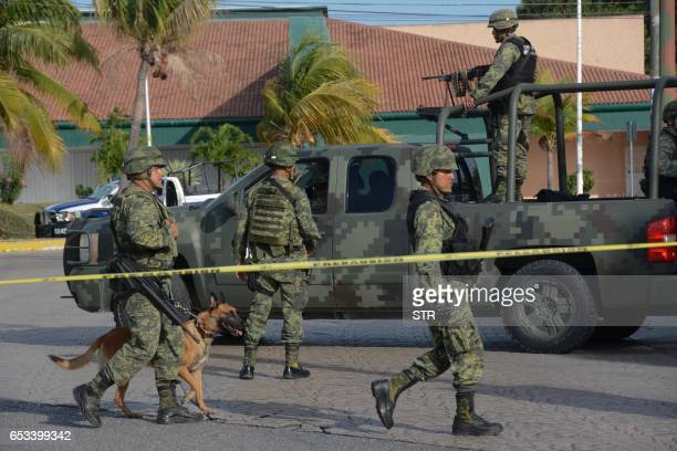 Mexican army soldiers patrol the site of an attack against a municipal police patrol car in Cancun Quintana Roo state Mexico on March 14 2017...