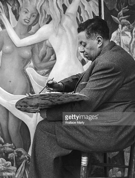 Mexican artist Diego Rivera sits on a stool while using an easel to paint a mural Rivera's murals address social themes especially those pertaining...