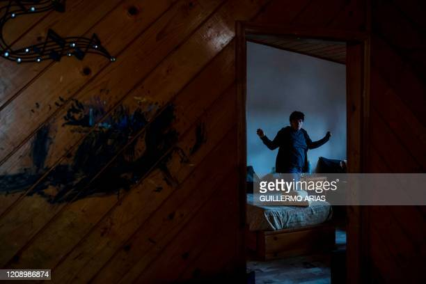 Mexican autistic Angel Arteaga walks around his room as he and his family quarantine at their home due to the COVID-19 outbreak in Tijuana, Baja...