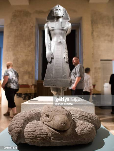 A Mexican Aztec sculpture of an eagle snake can be seen in front of a Pharao figure of Amenemhet III from the Middle Kingdom 12th Dynasty around...
