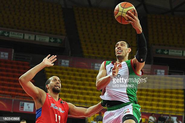 Mexican basketball player Gustavo Ayon is marked by Puerto Rican Ricardo Sanchez during their Final FIBA Championship game held in Caracas on...