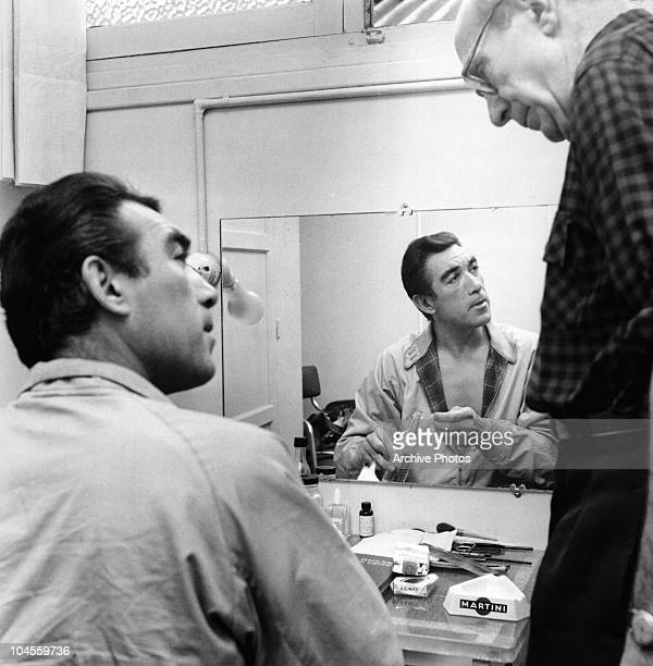 Mexican born American actor Anthony Quinn sitting in front of a mirror in his dressing room circa 1940s