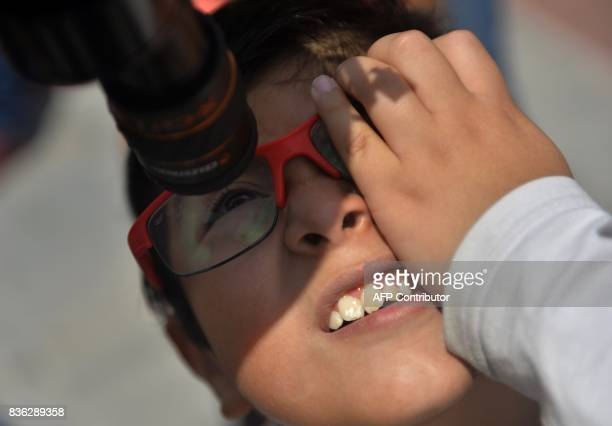A Mexican boy looks through a telescope at the beginning of the solar eclipse at the esplanade of the Museum of Natural History in Mexico City on...