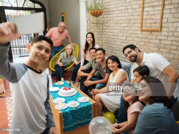 mexicaanse jongen die selfie met familie - nosotroscollection stockfoto's en -beelden