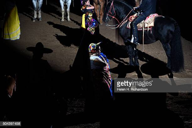 Mexican Charros and dancers put their hands to their hats as they listen to the Mexican Anthem during the 22nd annual Mexican Rodeo Extravaganza in...