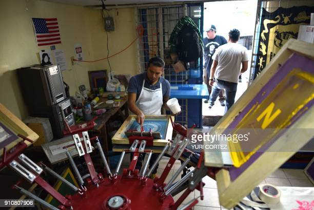 A Mexican citizen deported from the United States works at 'Deportados Brand' serigraphy workshop stamping Tshirts to sell for a living in Mexico...