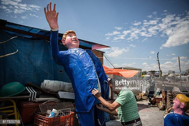 Mexican craftsman Felipe Linares holds a figure representing US Republican presidential candidate Donald Trump which will be burned during the...