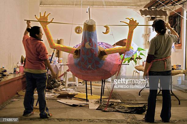 Mexican craftswoman Elsa Linares and assitant Yeudiel Lara work on an 'alebrije' called 'Head of Bird and Feet of Goat' in Mexico City for the 'Night...