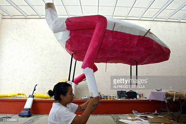 Mexican craftswoman Elsa Linares works on an 'alebrije' called 'Head of Bird and Feet of Goat' in Mexico City for the 'Night of Alebrijes' parade 17...