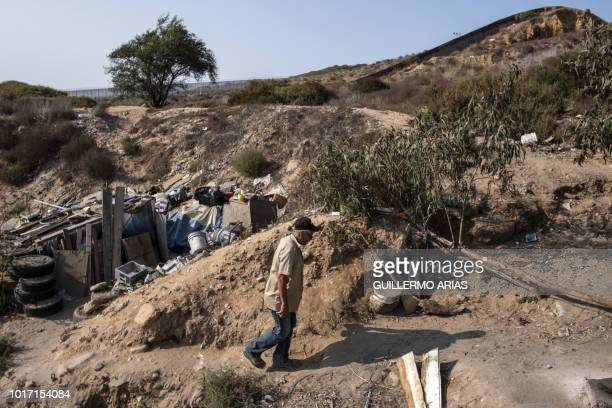 Mexican deported migrant Angel Ayala walks by his tent made out of waste materials at the Smuggler's Gulch near the MexicoUS border in Tijuana Baja...