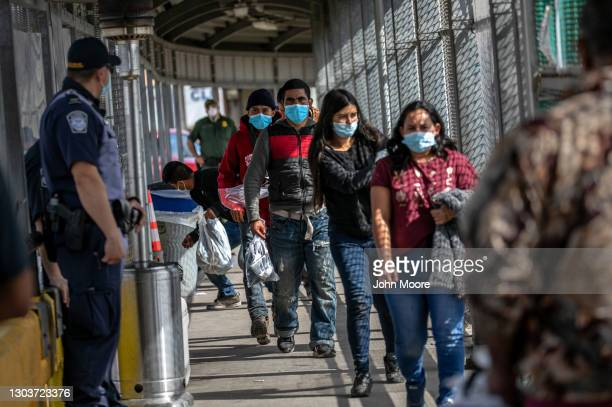 Mexican deportees walk across the U.S.-Mexico border bridge while being released by U.S. Immigration authorities into Mexico on February 23, 2021 in...