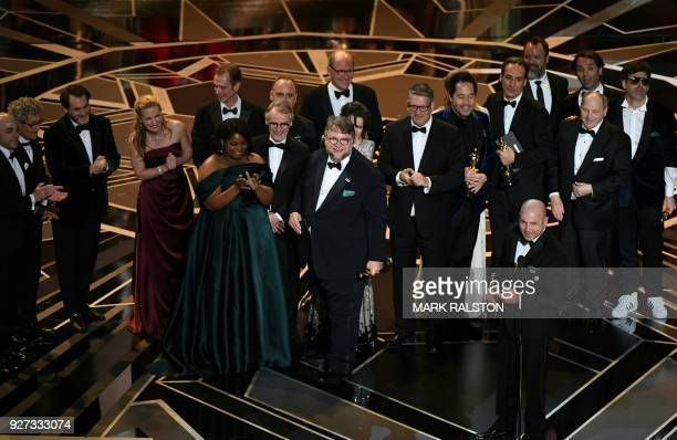 TOPSHOT Mexican director Guillermo del Toro stand on stage with his cast and crew after he won the Oscar for Best Film for 'The Shape of Water'...