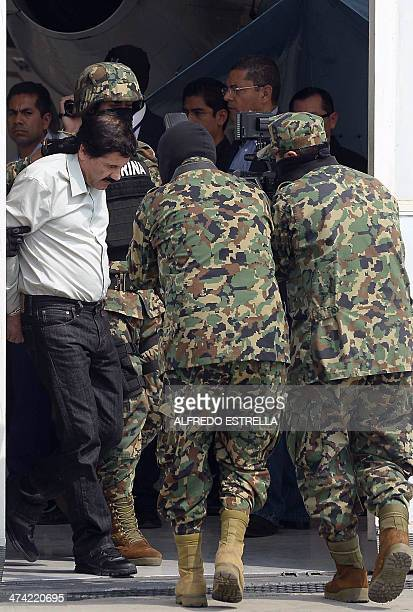 Mexican drug trafficker Joaquin Guzman Loera aka 'el Chapo Guzman' is escorted by marines as he is presented to the press on February 22 2014 in...