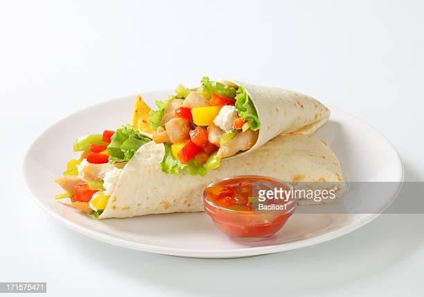 mexican fajitas (tortilla wraps) on a white plate