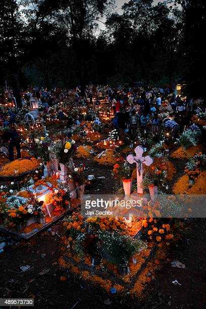 Mexican families gather at the cemetery lighting candles and bringing flowers to honor their deceased relatives during the Day of the Dead...