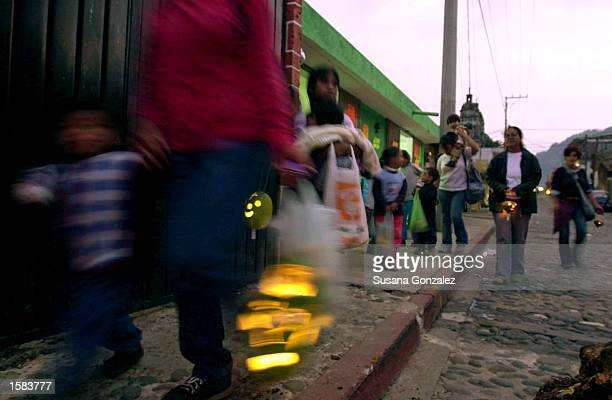 Mexican families walk the streets with pumpkin lamps during a local version of Trick or Treat November 1 2002 in Tepoztlan Mexico Mexicans observe...