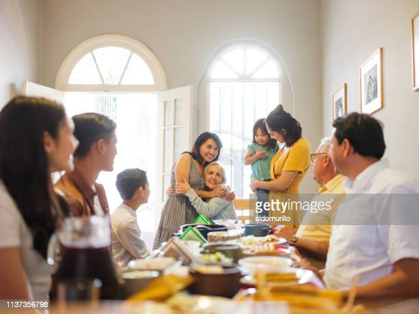 mexican family at lunch table embracing grandmother - tradition stock pictures, royalty-free photos & images