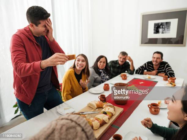 mexican family celebrating and laughing with rosca de reyes - roscon de reyes stock pictures, royalty-free photos & images