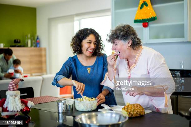 mexican family celebrating christmas, preparing food - mexican christmas stock photos and pictures