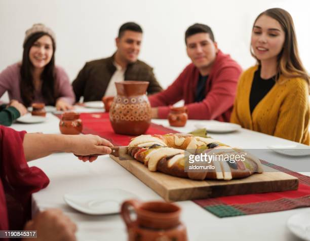 mexican family cutting traditional rosca de reyes at table - roscon de reyes stock pictures, royalty-free photos & images
