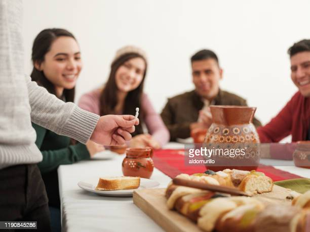mexican family looking at figurine of rosca de reyes on epiphany day - roscon de reyes stock pictures, royalty-free photos & images