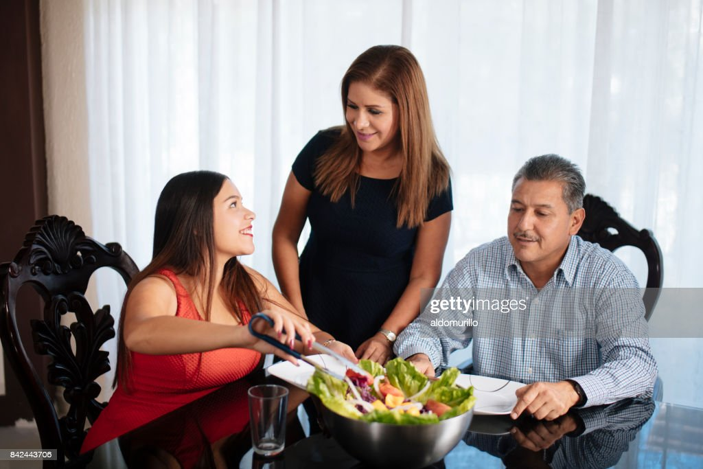 Mexican Family Of Three Eating Salad At Table Stock Photo