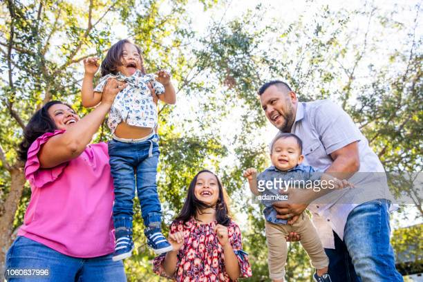 mexican family playing in the park - heavy stock pictures, royalty-free photos & images