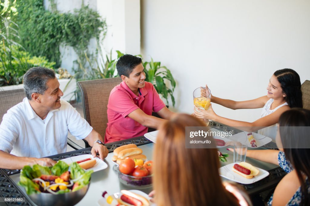 Mexican Family Sitting At The Table With Food Stock Photo