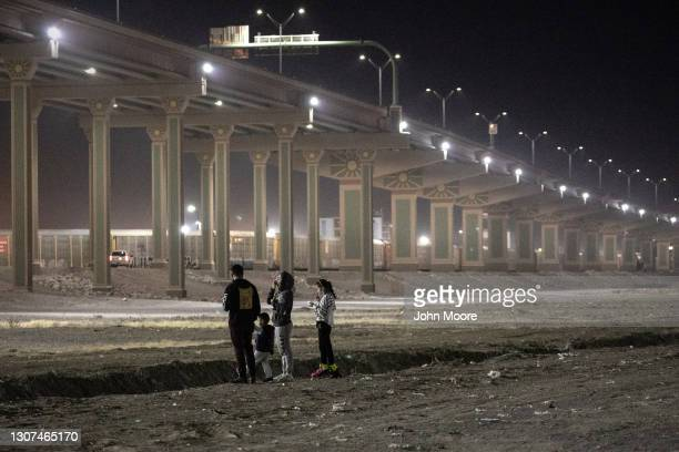 Mexican family stands along the bank of the Rio Grande at the U.S.-Mexico border on March 15, 2021 in Ciudad Juarez, Mexico. A surge of some 10,000...