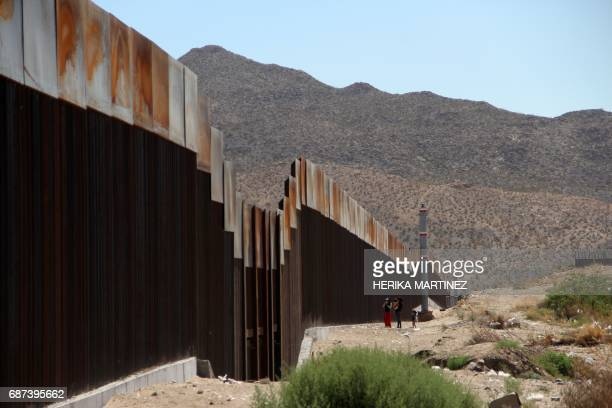 Mexican family stands next to the border wall between Mexico and the United States in Ciudad Juarez Mexico on May 23 2017 The United States is about...