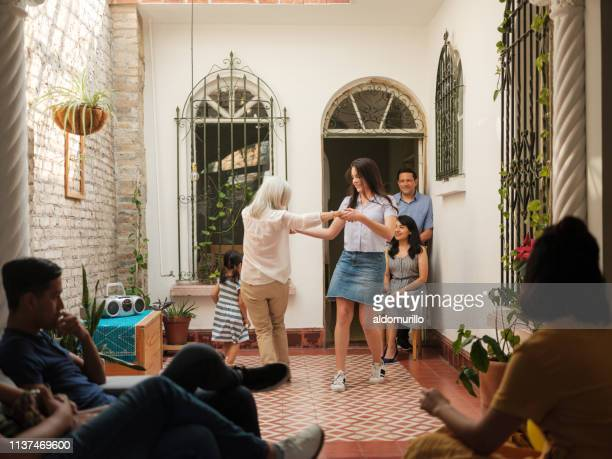 Mexican family watching grandmother dance with granddaughter