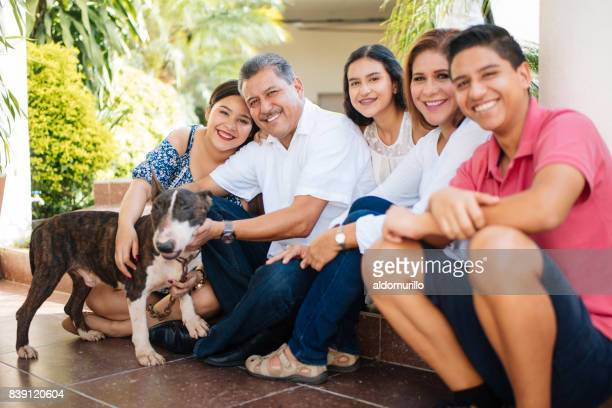 Mexican family with dog sitting on floor and smiling