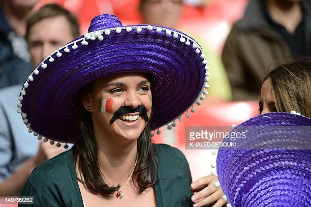 A Mexican fan with a fake moustache and wearing a sombrero smiles in the stands during the quarterfinal of Men's football match between Mexico and...
