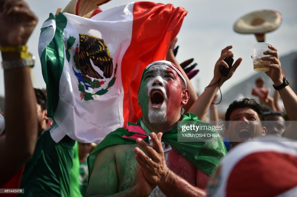 Mexican fans celebrate after Mexico scored a goal during their Round of 16 football match against the Netherlands as they watch the game at Fanfesta's live projection at Copacabana beach in Rio de Janeiro on June 29, 2014 during the 2014 FIFA World Cup tournament.