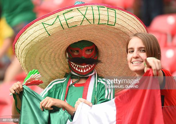 Mexican fans cheer before a Group A football match between Croatia and Mexico at the Pernambuco Arena in Recife during the 2014 FIFA World Cup on...