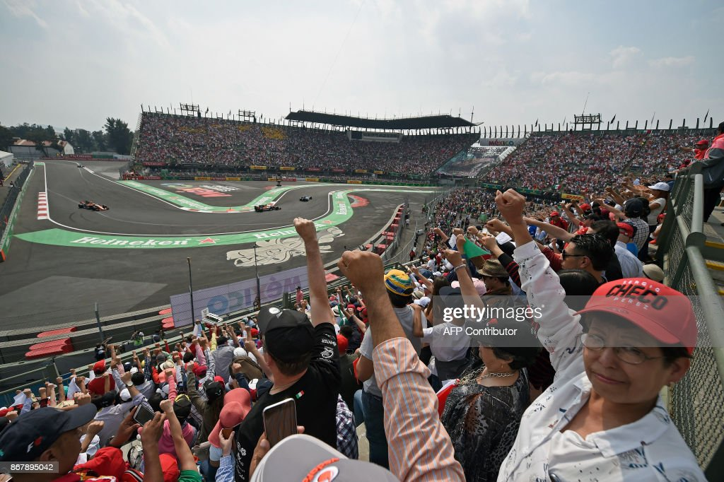 TOPSHOT - Mexican fans raise their clenched fists in tribute to the victims of September 19th quake, during the Formula One Mexico Grand Prix race at the Hermanos Rodriguez circuit in Mexico City on October 29, 2017. /