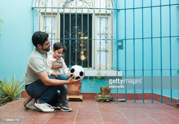 menino de abraço do pai mexicano no patamar e no futebol da terra arrendada - latino americano - fotografias e filmes do acervo