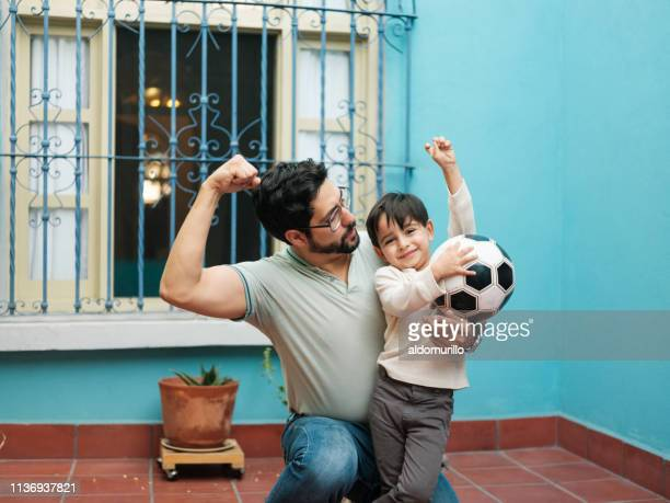 Mexican father flexing arm and showing to little son