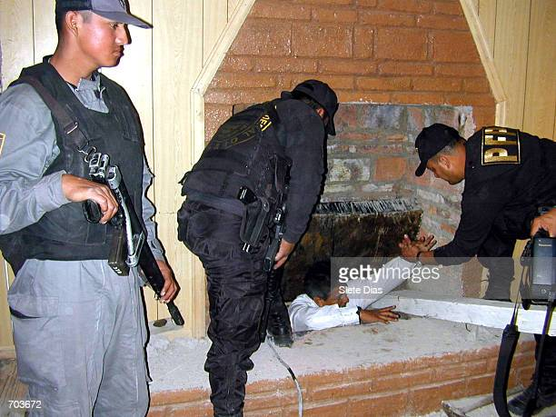 Mexican Federal Police officers check the interior of a chimney that serves as an entrtance to a tunnel discovered February 28 2002 that was used to...