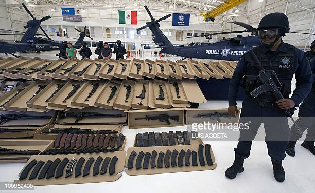 A Mexican Federal Police stands guard as embers of drug gang Los Zetas Margarito Mendoza and Carmen Zuniga are shown to the press in Mexico City on...