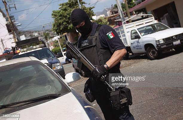 Mexican federal policeman inspects an abandoned car on March 1, 2012 in Acapulco, Mexico. Stolen vehicles used by drug gangs are often found...