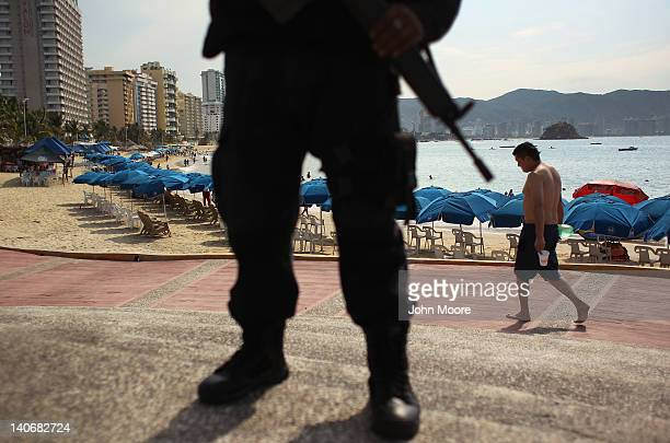 Mexican federal policeman stands guard near the beach on March 4 2012 in Acapulco Mexico Drug violence has surged in the coastal resort in the last...