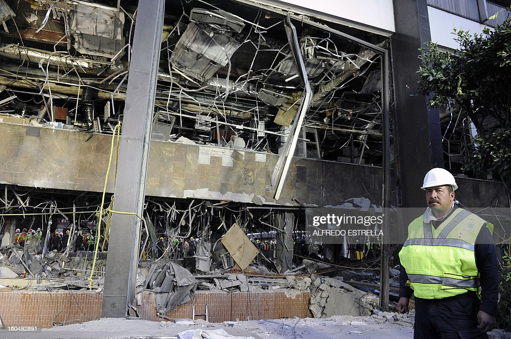 A Mexican federal policeman stands guard next to the damaged building inside the premises of state-owned Mexican oil giant Pemex, following a blast on the eve, in Mexico City on February 1, 2013. An explosion rocked the skyscraper, leaving up to 33 dead and 121 injured. Hundreds of firefighters, police and soldiers toiled through the night after the blast ripped through an annex of the 54-floor tower leaving concrete, computers and office furniture strewn on the ground. AFP PHOTO/Alredo Estrella