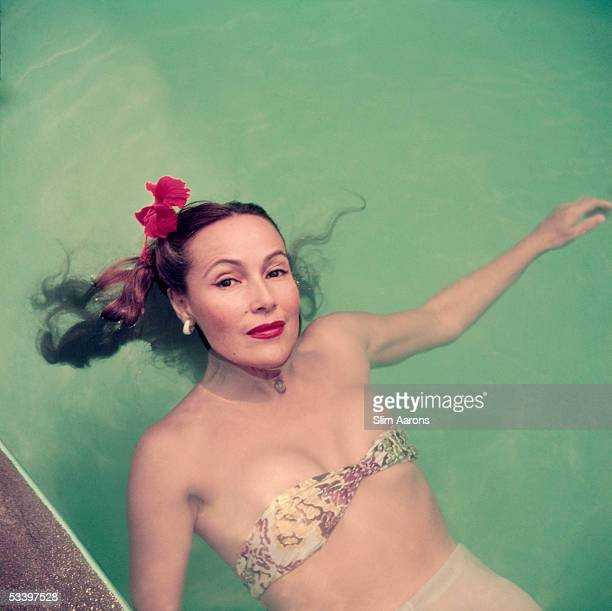 Mexican film star Dolores Del Rio floating in a swimming pool in Acapulco 1952
